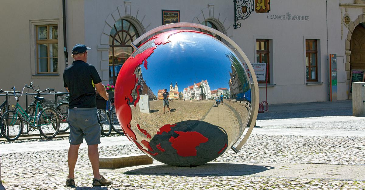 Ein Mann steht vor der verchromten Kugel der Weltausstellung Reformation in Wittenberg