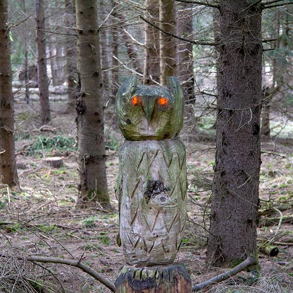 Eine Holz-Eule im Wald