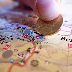 Mit einer Münze wird eine Stempelstelle auf dem Rubbelposter der Harzer Wandernadel freigerubbelt