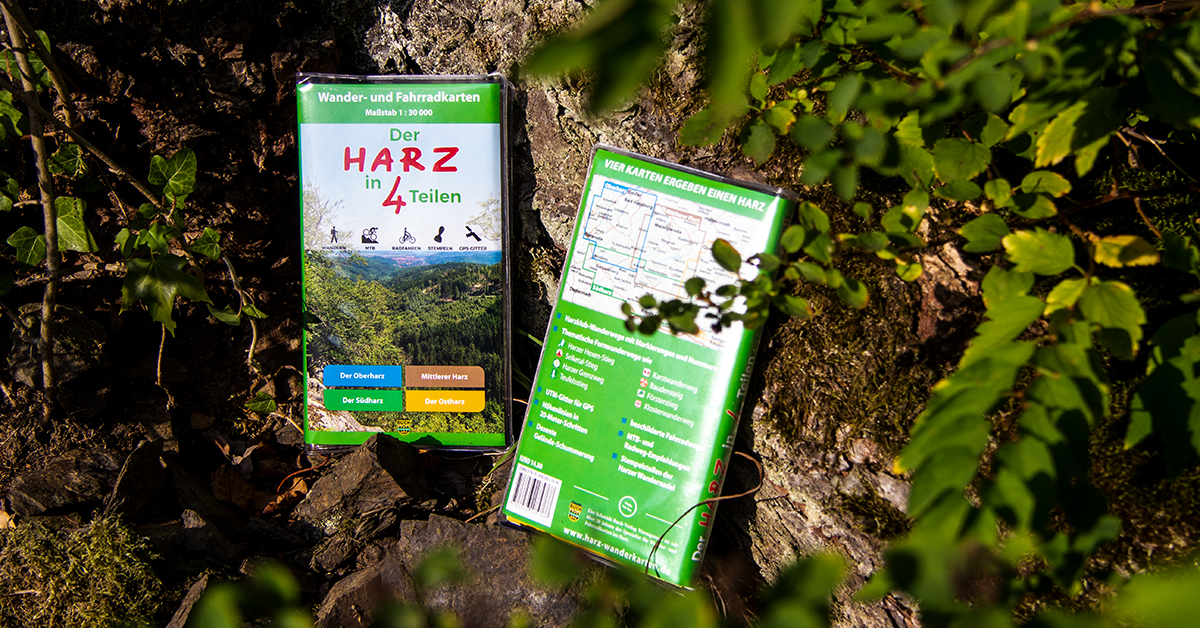 """Wanderkarten-Set """"Der Harz in 4 Teilen"""" liegt an einem Baumstumpf"""