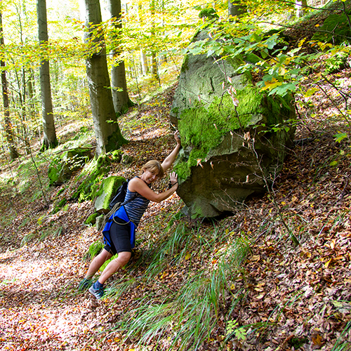 Eine Wanderin hält einen Felsen am Hang