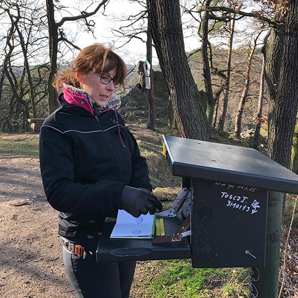 Eine Wanderin am Stempelkasten im Harz